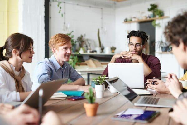 quattro ragazzi creano un network professionale seduti insieme intorno a un tavolo