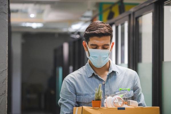 giovane con mascherina affronta la perdita del lavoro come opportunità